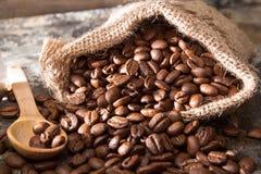 Feijões de café Roasted no saco pequeno na superfície de metal fotografia de stock royalty free