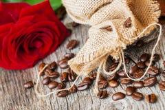 Feijões de café Roasted, rosa fresca do vermelho, saco grosseiro de serapilheira na tabela de madeira velha Do vintage vida ainda Imagem de Stock