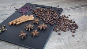 Feijões de café, varas de canela e anis de estrela Especiarias e alimento na tabela de madeira Ingredientes para fazer o café fotografia de stock royalty free