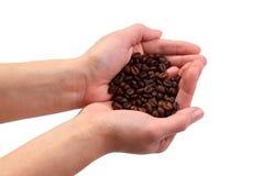 Feijões de Coffe nas mãos Fotografia de Stock Royalty Free