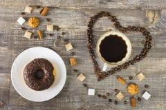 Feijões do copo de café sob a forma do coração em uma tabela de madeira Pão-de-espécie do açúcar Imagem de Stock Royalty Free