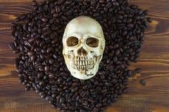 Feijões do crânio e de café isolados no fundo de madeira Imagens de Stock Royalty Free