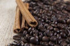 Feijões e canela de café na tabela de madeira Fotos de Stock Royalty Free