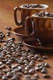 Feijões e copos de café Imagens de Stock