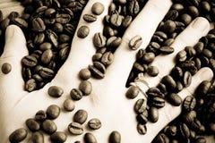 Feijões e mão de café Fotografia de Stock Royalty Free