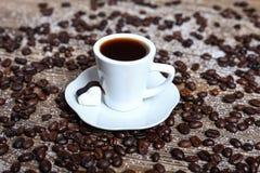 Feijões frescos da xícara de café e de café na tabela Fotografia de Stock Royalty Free