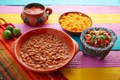 Feijões mexicanos de Frijoles com arroz e molhos fotografia de stock royalty free