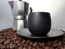 Feijões pretos do copo e de café do café Fotografia de Stock Royalty Free