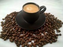 Feijões pretos do copo e de café do café Imagem de Stock Royalty Free