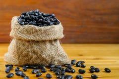 Feijões pretos no saco do cânhamo no fundo de madeira Os feijões pretos têm h Foto de Stock Royalty Free