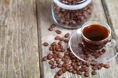 Feijões transparentes da xícara de café e de café com o banco Fotos de Stock
