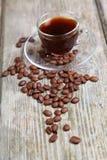 Feijões transparentes da xícara de café e de café com o banco Imagem de Stock