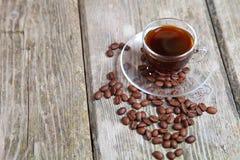 Feijões transparentes da xícara de café e de café com o banco Imagens de Stock Royalty Free