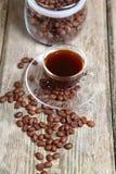 Feijões transparentes da xícara de café e de café com o banco Foto de Stock Royalty Free