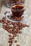 Feijões transparentes da xícara de café e de café com o banco Imagens de Stock