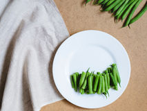 Feijões verdes cortados em uma placa branca e um grupo dos feijões verdes o Imagem de Stock