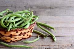 Feijões verdes crus em uma cesta de vime marrom e em um fundo de madeira velho Alimento cru da dieta Alimento do vegetariano Imagens de Stock Royalty Free