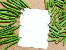 Feijões verdes e feijões verdes cortados na tabela com um branco Foto de Stock