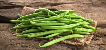 Feijões verdes na placa de corte de madeira, em branco, alimento do vegetariano foto de stock