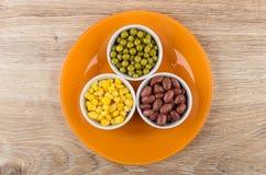Feijões vermelhos, ervilhas verdes e milho doce na placa alaranjada Imagens de Stock Royalty Free
