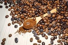 Feij?es de caf? e caf? ? terra na colher de madeira imagem de stock royalty free
