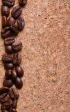 Feijões de café em um fundo da textura do corkwood Imagens de Stock Royalty Free