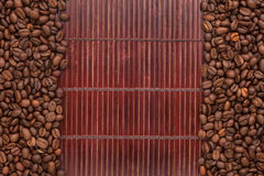 Feijões de café que encontram-se em uma esteira de bambu Fotografia de Stock Royalty Free