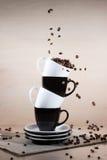 Feijões de café Roasted que caem para baixo em copos preto e branco na pilha das placas que estão no jornal Foto de Stock Royalty Free