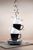 Feijões de café Roasted que caem para baixo em copos preto e branco na pilha das placas que estão no jornal Imagens de Stock