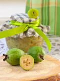 Feijoa on a background of cans of fruit puree Royalty Free Stock Photos
