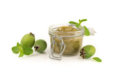 Feijoa jam in a jar made of fresh berries on white background. Royalty Free Stock Images