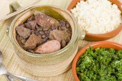 Feijoada. Brazilian beef, sausage, pork and black bean stew served with manioc flour, kale and white rice Stock Photo