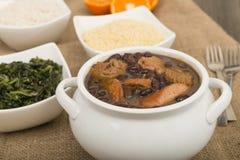 Feijoada. Brazilian beef, sausage, pork and black bean stew served with manioc flour, kale, white rice and oranges stock photos