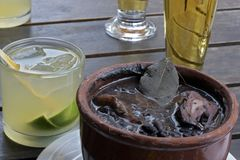 Feijoada, traditional Brazilian bean stew, with caipirinha cup. Feijoada, traditional bean stew typical of Brazilian cuisine, accompanied by caipirinha, the most stock image