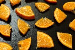 Fein geschnittene Tangerinen auf einem schwarzen Hintergrund stockbild