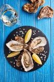 Feine Austern de Claire mit Zitrone und Weißwein lizenzfreie stockfotos