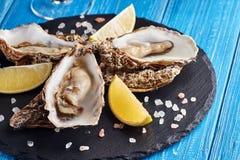Feine Austern de Claire mit Zitrone und Weißwein stockfotografie