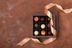 Feine Schokoladen im Handwerkskasten mit Satinband auf einem dunklen Hintergrund Flacher Plan Festliches Konzept Kopieren Sie Pla lizenzfreies stockbild
