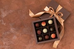 Feine Schokoladen im Handwerkskasten mit Satinband auf einem dunklen Hintergrund Platz für Design Flacher Plan Festliches Konzept stockfotos