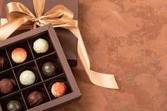Feine Schokoladen im Handwerkskasten mit Satinband auf einem dunklen Hintergrund Platz für Design Flacher Plan Festliches Konzept stockfotografie