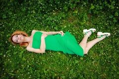 Feines blondes Lügen auf dem Gras, schön verbogen, schauend im Nocken Stockfotografie