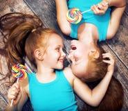 Feines Porträt, das von den Zwillingsschwestern halten Lutscher ist lizenzfreie stockfotos