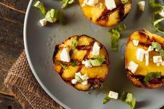 Feinschmecker gebratene Pfirsiche mit Käse und Basilikum stockfoto