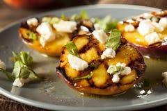 Feinschmecker gebratene Pfirsiche mit Käse und Basilikum stockbild