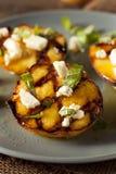 Feinschmecker gebratene Pfirsiche mit Käse und Basilikum lizenzfreie stockbilder