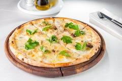 Feinschmeckerische Pizza mit weißen Pilzen Gorgonzola und des porcini, die mit Petersilie verziert werden, verlässt auf dem hölze Stockfotos