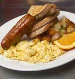 Feinschmeckerisches Frühstück mit Wurst und durcheinandergemischten Eiern Stockfotografie