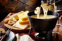Feinschmeckerisches Schweizer Fondue-Essen an einem Winterabend stockfoto