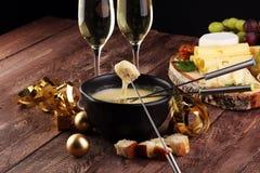 Feinschmeckerisches Schweizer Fondue-Essen an einem Winterabend mit sortierten Käsen auf einem Brett neben einem erhitzten Topf d lizenzfreie stockbilder
