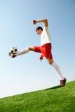 Feint. Portrait of soccer player kicking ball on football field Royalty Free Stock Photo